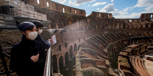 Tourists with masks visiting the Colosseum in Rome on Saturday. (AP Photo/Andrew Medichini)