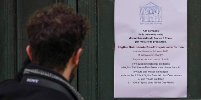 A man reads a note announcing the closing of the St. Louis of the French church in Rome, Sunday, March 1, 2020. The French community church in Rome, St. Louis of the French, closed its doors to the public on Sunday, reportedly after a priest was infected with coronavirus.