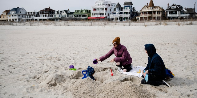 Matt and Anna Mason play with their son, Oliver, on the beach in Cape May, N.J., Wednesday, March 18, 2020. The Masons live and work in Cape May.