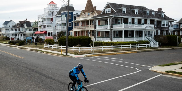 A cyclist rides a bicycle in Cape May, N.J., Wednesday, March 18, 2020.