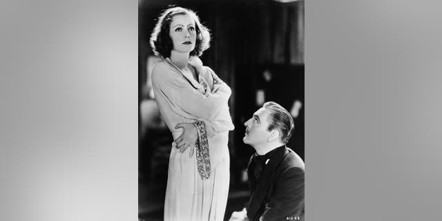 """John Barrymore (1882 - 1942) contrives to seduce the eccentric Greta Garbo (1905 - 1990) in a scene from the film """"Grand Hotel,"""" directed by Edmund Goulding for MGM."""