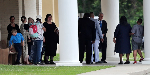 Congregants gather after services at the Life Tabernacle Church in Central, La., Sunday, March 29, 2020. Pastor Tony Spell has defied a shelter-in-place order by Louisiana Gov. John Bel Edwards, due to the new coronavirus pandemic, and continues to hold church services with hundreds of congregants. (AP Photo/Gerald Herbert)