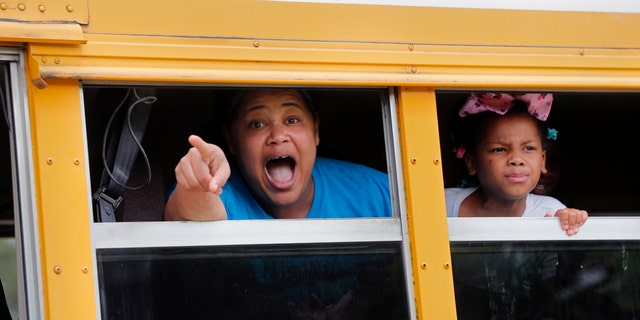 A congregant in a church bus yells out to news media as they leave services at the Life Tabernacle Church in Central, La., Sunday, March 29, 2020. Pastor Tony Spell has defied a shelter-in-place order by Louisiana Gov. John Bel Edwards, due to the new coronavirus pandemic, and continues to hold church services with hundreds of congregants. (AP Photo/Gerald Herbert)