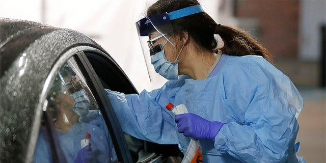 A nurse at a drive-up coronavirus testing station set up by the University of Washington Medical Center uses a swab to take a sample from the nose of a person in a car Friday, March 13, 2020, in Seattle. (Associated Press)