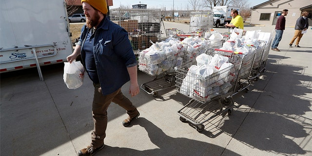 In this Tuesday, March 17, 2020, photo Patrick Minor loads food onto a delivery truck at the Des Moines Area Religious Council food pantry in Des Moines, Iowa. With the new coronavirus leaving many people at least temporarily out of work, food banks and pantries across the U.S. are scrambling to meet an expected surge in demand, even as older volunteers have been told to stay home and calls for social distancing have complicated efforts to package and distribute food.