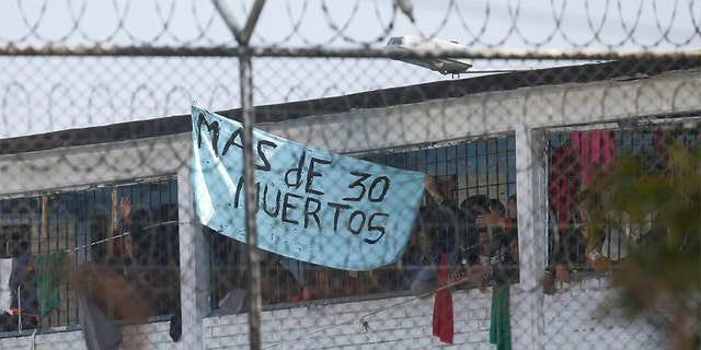 "Inmates display a sign reading in Spanish ""More than 30 dead"" at La Modelo jail in Bogota, Colombia, Sunday, March 22, 2020. Violence broke out in the prison out of inmates' fears that authorities are not doing enough to prevent coronavirus inside overcrowded prisons. (AP Photo/Ivan Valencia)"