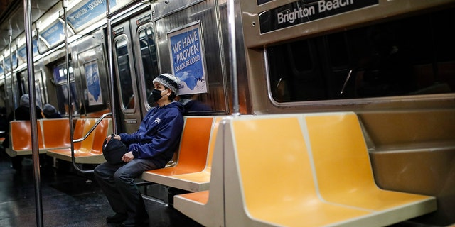 A commuter wears a face mask while riding a nearly empty subway car into Brooklyn, Thursday, March 12, 2020, in New York. New York City Mayor Bill de Blasio said Thursday he will announce new restrictions on gatherings to halt the spread of the new coronavirus in the coming days, but he hopes to avoid closing all public events such as Broadway shows. For most people, the new coronavirus causes only mild or moderate symptoms. For some it can cause more severe illness.