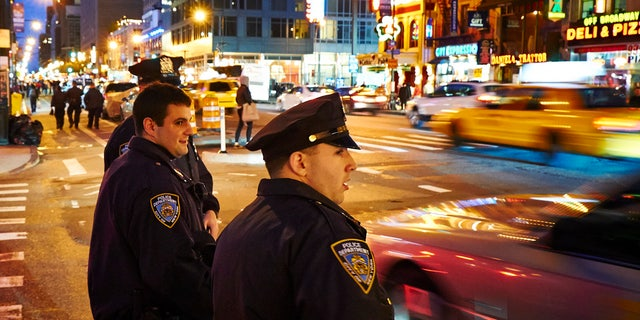 New York, USA - May 21, 2013: Three NYPD Police officers patrols streets of Manhattan in New York City at night.