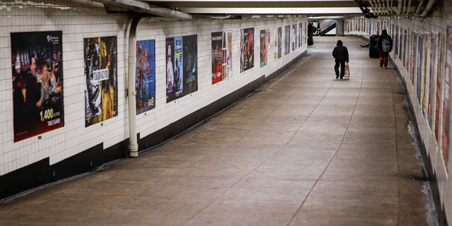A subway customer walks through an empty underground passage in the Brooklyn borough of New York, Monday, March 16, 2020.