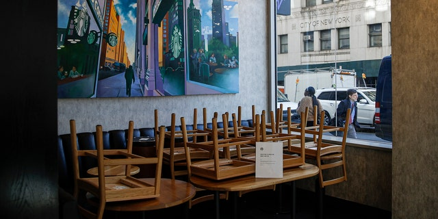 Chairs are stacked in a Starbucks coffee shop that remained open for customers purchasing for take-away, Monday, March 16, 2020, in New York.