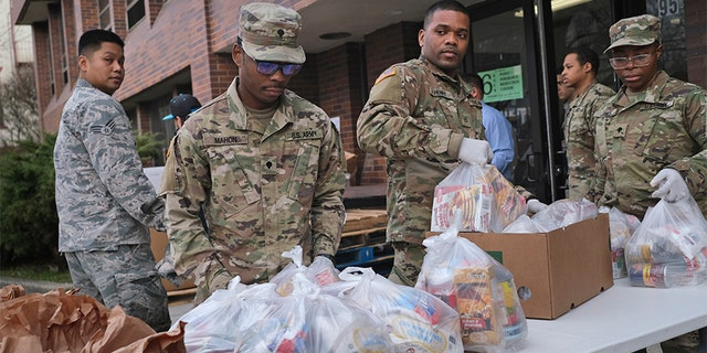 """Members of the New York National Guard help to organize and distribute food to families on free or reduced school lunch programs in New Rochelle, N.Y., Thursday, March 12, 2020. State officials have set up a """"containment area"""" in the New York City suburb. (AP Photo/Seth Wenig)"""