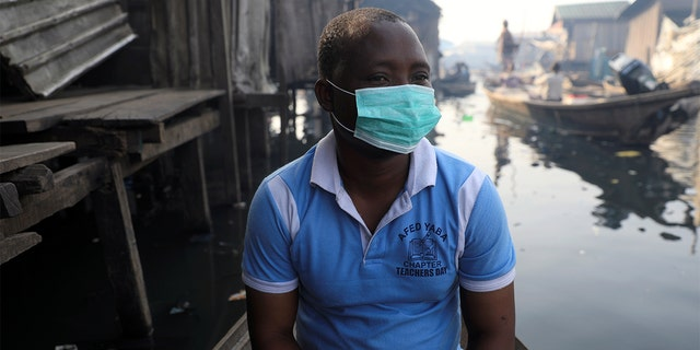 A man wearing a face mask sits in a traditional canoe at the Makoko community in Lagos, Nigeria March 9, 2020. (REUTERS/Temilade Adelaja)