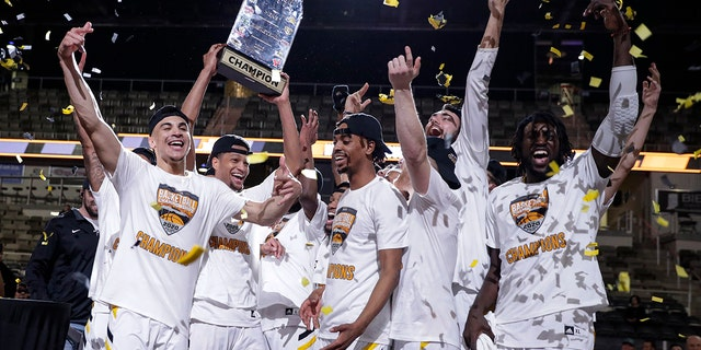 Northern Kentucky celebrates with the trophy after a 71-62 win over Illinois-Chicago in an NCAA college basketball game for the Horizon League men's tournament championship in Indianapolis, Tuesday, March 10, 2020. (AP Photo/Michael Conroy)