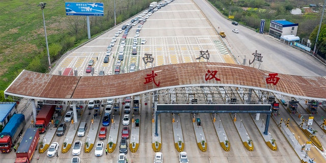 In this March 24, 2020, photo released by Xinhua News Agency, an aerial photo shows vehicles waiting to cross into Wuhan at a highway toll station in Wuhan, in central China's Hubei Province. Hubei has ended a lockdown for most of the province, allowing people who have passed health checks to leave for the first time in two months. The provincial capital of Wuhan, where the virus hit hardest, remains locked down until April 8. (Cai Yang/Xinhua via AP)