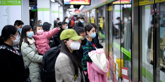 People wearing face masks wait for a subway train on the first day the city's subway services resumed following the novel coronavirus disease (COVID-19) outbreak, in Wuhan of Hubei province, on March 28, 2020.  REUTERS/Aly Song