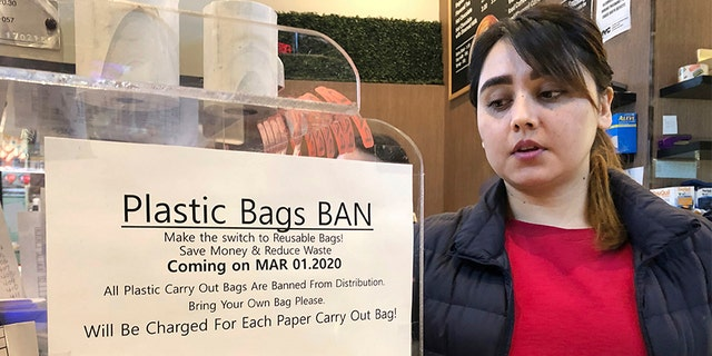 """A cash register attendant looking at a sign reading """"Plastic Bags Ban"""" in a grocery store in New York last Wednesday. (AP Photo/Ted Shaffrey)"""