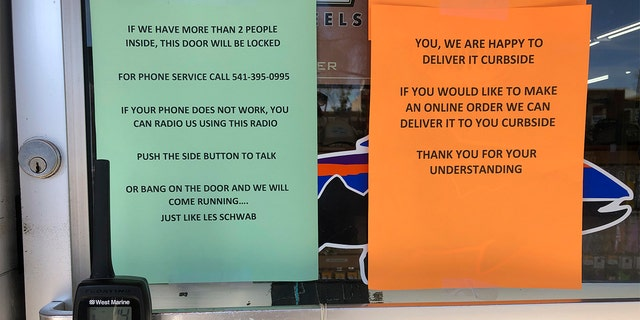 In this photo taken March 20, 2020, a sign outside a fly fishing shop in tiny Maupin, Oregon, advises customers of new policies to limit the spread of the new coronavirus in rural areas. (AP Photo/Gillian Flaccus)