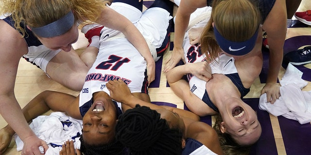 Samford guards Charity Brown (12) and Sarah Myers (25) fall to the floor to celebrate with teammates after their win over UNC Greensboro for the NCAA women's college basketball Southern Conference championship tournament, Sunday, March 8, 2020, in Asheville, N.C. (AP Photo/Kathy Kmonicek)