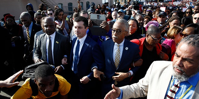 """Democratic presidential candidate and former South Bend, Ind. Mayor Pete Buttigieg and the Rev. Al Sharpton, walk across the Edmund Pettus Bridge in Selma, Ala., Sunday, March 1, 2020, to commemorate the 55th anniversary of """"Bloody Sunday,"""" when white police attacked black marchers in Selma. (AP Photo/Patrick Semansky)"""