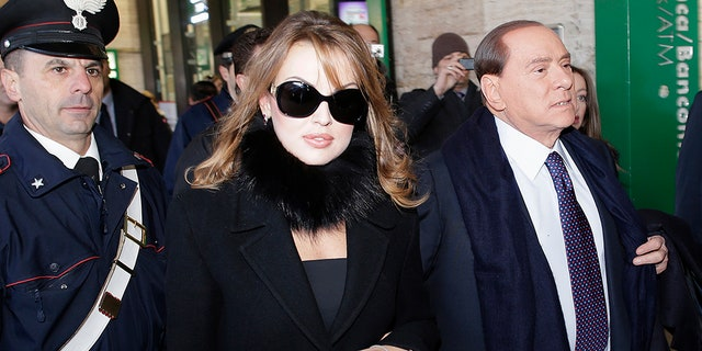 Former Italian Prime Minister Silvio Berlusconi (R) and his fiancee Francesca Pascale walk at the Rome train station December 29, 2012. REUTERS/Tony Gentile (ITALY - Tags: POLITICS) - GM1E8CT1DHV01