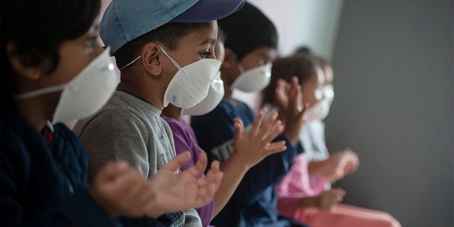 Learners wear masks as they sanitise their hans at a pre-school in Lenasia, Johannesburg, Tuesday, March 17, 2020, on the day schools closed in a bid to control the spread of coronavirus. (AP Photo/Shiraaz Mohamed)