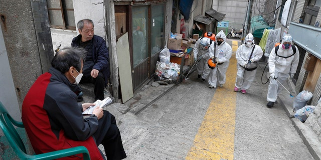 Workers spray disinfectant as a precaution against coronavirus in Seoul, South Korea, Wednesday, March 25, 2020.