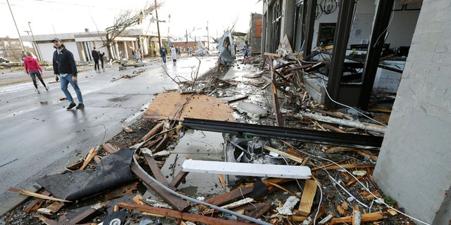 People pass by businesses destroyed by storms Tuesday, March 3, 2020, in Nashville, Tenn.