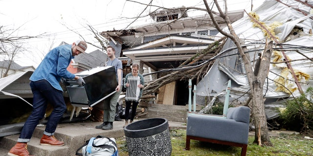 Benji Peck, left, and Austin Grove remove a refrigerator from a damaged home Wednesday, March 4, 2020, in Nashville, Tenn. Residents and businesses face a huge cleanup effort after tornadoes hit the state Tuesday.