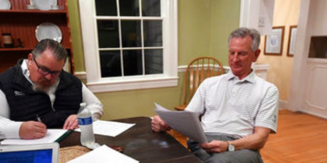 Alabama U.S. Senate candidate Tommy Tuberville, right, watches election returns and works on his speech in the main house at Auburn Oaks Farm, the site of his election party, Tuesday, March 3, 2020. Tuberville is in a tight race with seven competitors for the Senate seat. (Joe Songer/The Birmingham News via AP)