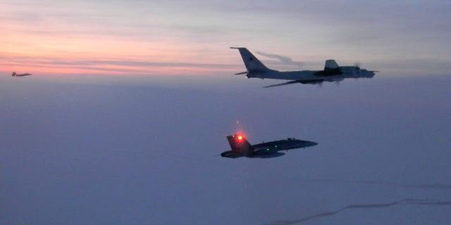 A Russian Tu-142, top right, was intercepted near the Alaskan coastline, officials said. (North American Aerospace Defense Command via AP)