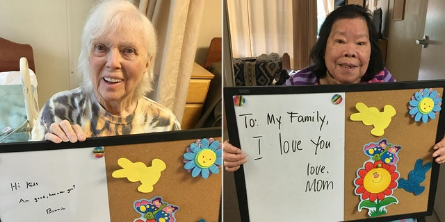 Two residents smile as they hold up signs with messages written to their families,