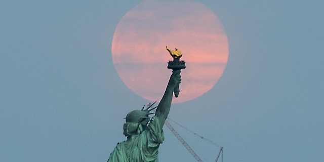 The 'Super Worm Equinox Moon' rises behind the Statue of Liberty in New York, on March 20, 2019.
