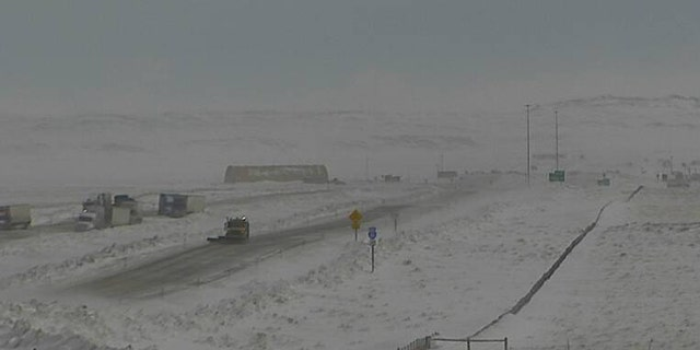 Trucks can be seen parked int he area of a major pileup on Interstate 80 in Wyoming on Monday.