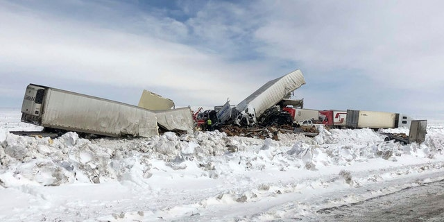 Wrecked tractor-trailers remain on the scene Monday, March 2, 2020, following Sunday's accident, on Interstate 80 in south central Wyoming.