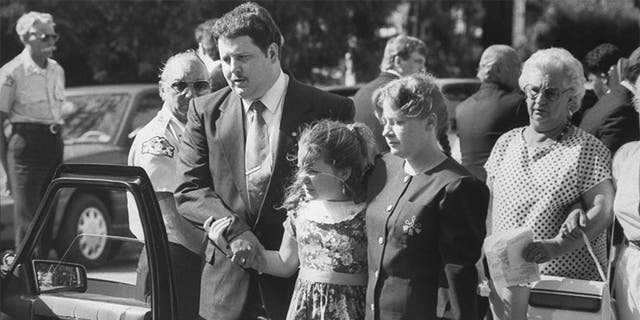 Todd and Diana Moore, parents of murder victim Michael Moore, with 9-yr-old daughter Dawn walking outside the Holy Cross Episcopal Church at Michael's funeral.