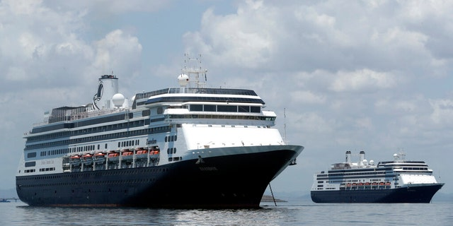 The Zaandam cruise ship, left, and the Rotterdam, seen here outside of Panama last week, are currently waiting to disembark in Florida. (AP Photo/Arnulfo Franco)