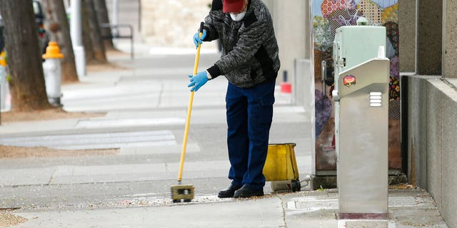 A man cleans a sidewalk in downtown Sacramento, Calif., Monday, March 23, 2020. (AP)
