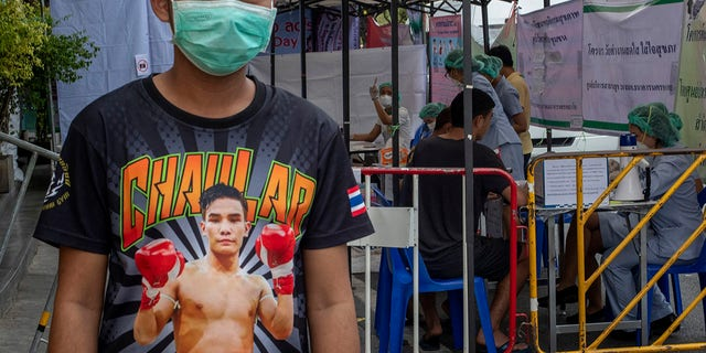 AMuay Thai boxing fighter stands in front of makeshift screening facility outside Rajadamnern boxing stadium in Bangkok, Thailand, March 19, 2020. (Associated Press)