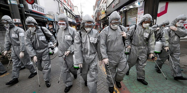 Army soldiers wearing protective suits spray disinfectant as a precaution against the new coronavirus at a shopping street in Seoul, South Korea, Wednesday, March 4, 2020. (AP Photo/Ahn Young-joon)