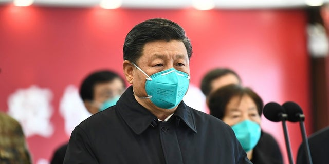 In this photo released by China's Xinhua News Agency, Chinese President Xi Jinping talks by video with patients and medical workers at the Huoshenshan Hospital in Wuhan in central China's Hubei Province earlier this month.  (Xie Huanchi/Xinhua via AP)
