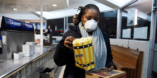 Andrea Wyatt of Inglewood, Calif., wears a mask as she collects her concessions at the Paramount Drive-In Theatres, Thursday, March 19, 2020, in Paramount, Calif. (AP Photo/Chris Pizzello)