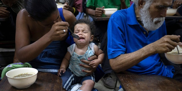 Zoraida Silva, 26, feeds her six month baby Jhon Angel, at a soup kitchen in The Cemetery slum, in Caracas, Venezuela. Silva said that she can not afford to have 3 meals a day, and she has been eating at the soup kitchen for two years ago. According to a survey recently published by the U.N. World Food Program, one of every three Venezuelans cope with food insecurity, unable to get enough food to meet their basic dietary needs. (AP Photo/Ariana Cubillos)