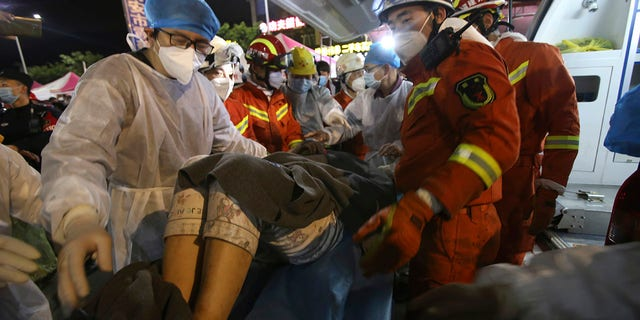 In this March 9, 2020, photo released by Xinhua News Agency, rescuers carry a woman pulled from the rubbles of a collapsed hotel to an ambulance in Quanzhou, southeast China's Fujian Province. Several have been killed and others trapped when in the collapsed Chinese hotel that was being used to isolate people who had arrived from other parts of China hit hard by the coronavirus outbreak, authorities said Sunday. (Zeng Demeng/Xinhua via AP)