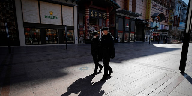 In this Tuesday, March 10, 2020, security guards patrolling the quiet Wangfujing shopping, a usually popular tourist spot before the new coronavirus outbreak in Beijing.