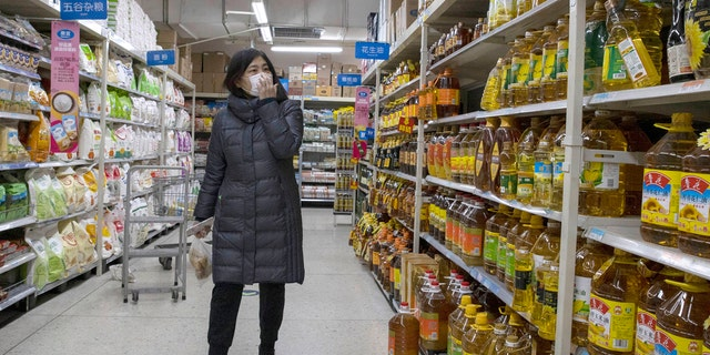 A shopper wearing a face mask browses an aisle of cooking oil in a supermarket in Beijing on Monday, March 16, 2020.