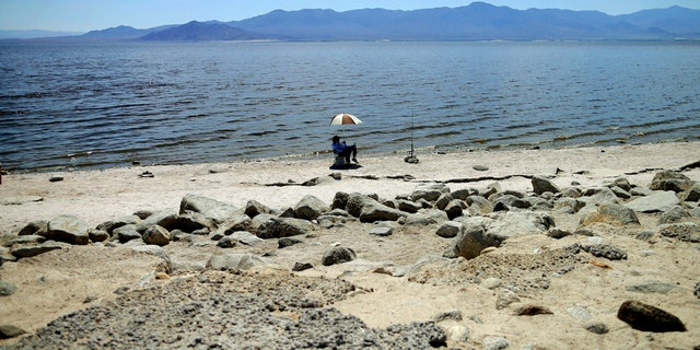 A man fishes along the back of the Bank of the sea of low-lying areas near Bombay Beach, California in 2015. (AP photo/Gregory Bull, file)