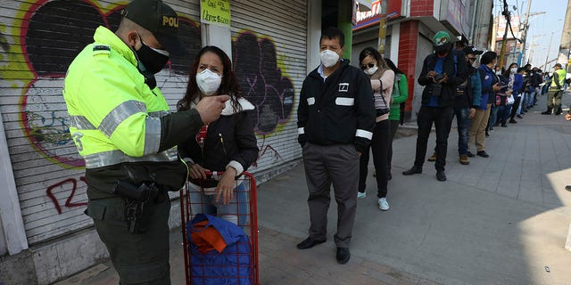 A police officer looks at woman's identification at a public bus station in Soacha on the outskirts of Bogota on Friday. Authorities have called for a complete lockdown of the country to help contain the spread of the new coronavirus, allowing residents to be outside their homes according to their ID numbers. (AP Photo/Fernando Vergara)