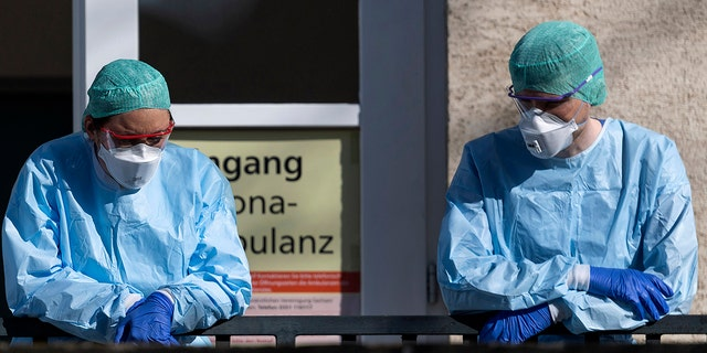 Employees of the Corona Outpatient Clinic at the University Hospital stand in protective clothing and breathing masks in front of the entrance in Dresden, Germany, on Wedneday. (Robert Michael/dpa via AP)