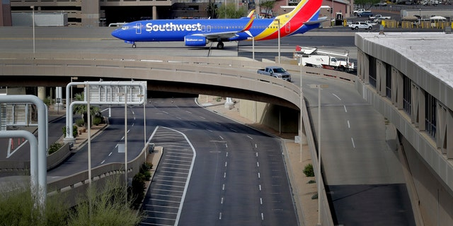A lone vehicle passes by an arriving jet Wednesday, March 25, 2020, at a typically active Sky Harbor International Airport in Phoenix.