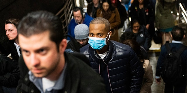 A man wearing a protective mask is seen on a subway platform on March 9, 2020, in New York City. (Jeenah Moon/Getty Images)